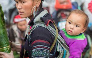 Hmong kvinna med ett barn på marknaden i Sapa