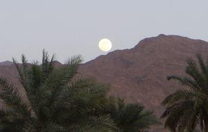Månen stiger upp över bergen